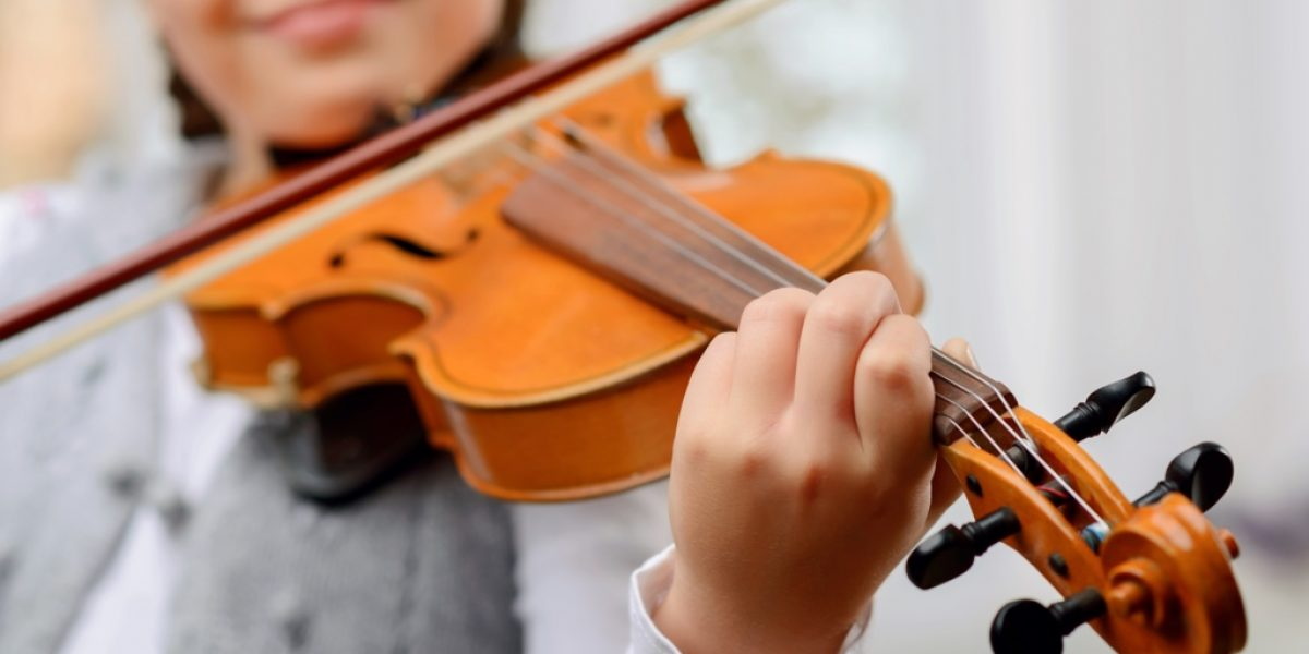 A way to success. Close up of pleasant vivacious pretty girl holding fiddle bow and learning to play the violin